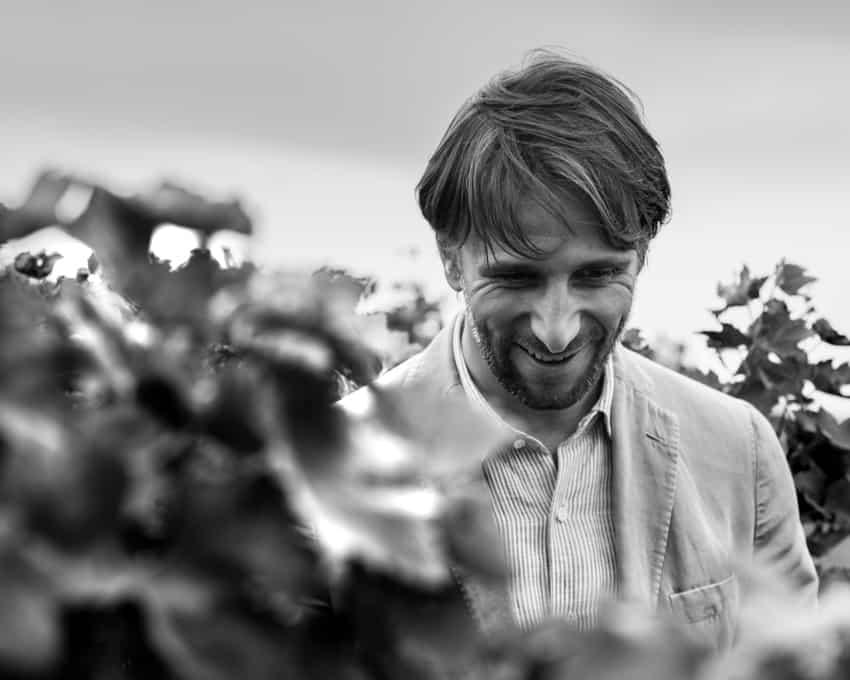 Pasquan viinintekijä, toimitusjohtajan serkku Giovanni Nordera tyytyväisenä Mai dire mai-köynnösten ympäröimänä.